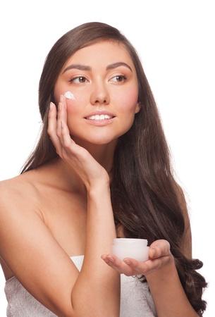 Portrait of young beautiful caucasian woman applying moisturizing cream. Isolated on white background Stock Photo
