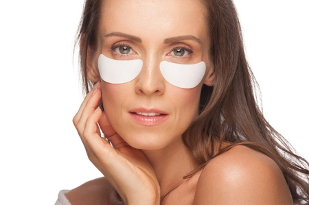 Closeup portrait of beautiful caucasian woman applying gel eye mask . Middle Aged Stock Photo