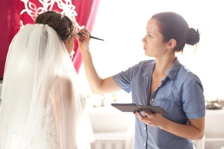 nude bride: Beautiful bride applying wedding make-up by professional make-up artist