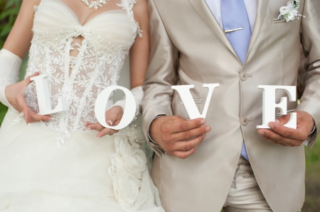 Closeup shot of bride and groom hands holding the word Love photo