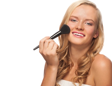 Portrait of young beautiful woman applying makeup. Pretty woman with makeup brush, isolated on white photo