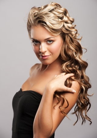 Studio portrait of attractive young woman with long blond hair and beautiful stylish hairstyle photo