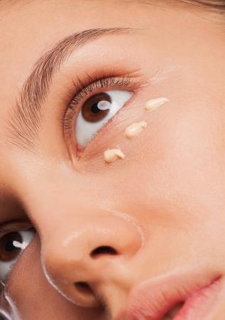 Closeup shot of beautiful young woman applying foundation on her face. Woman applying makeup photo