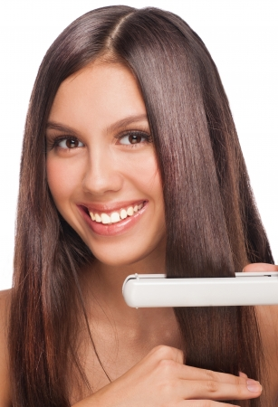 Beautiful woman with long straight hair holding hair straightening irons. Healthy hair. Hairstyling. Hairdressing.  photo