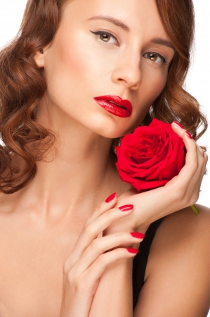 Portrait of young beautiful woman with red lipstick holding red rose. Isolated on white background photo