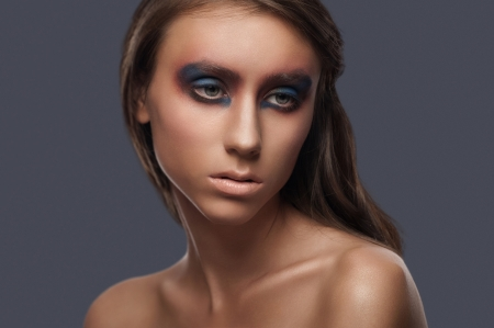 Closeup portrait of attractive young woman with bright creative makeup photo