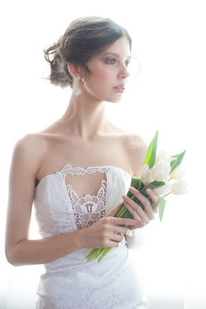 Portrait of young beautiful bride with bouquet of white tulips in her wedding day photo
