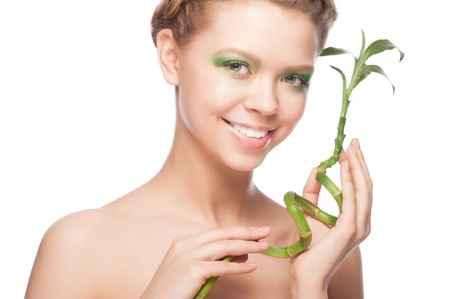Close-up portrait of beautiful young woman with green bamboo. Isolaton white background photo