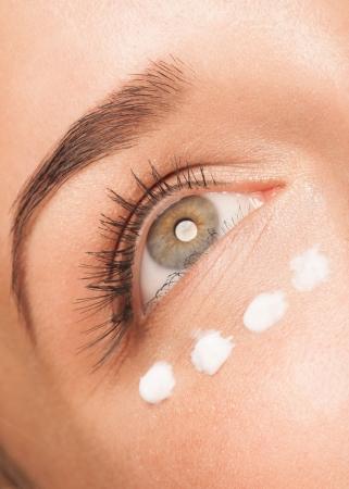 Closeup of beautiful woman eye. Woman applying moisturizing cream photo