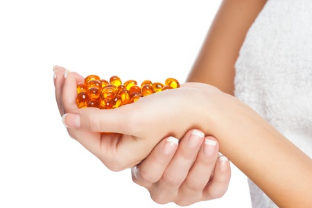 Closeup image of woman hands holding vitamin pillls. Isolated on white background photo