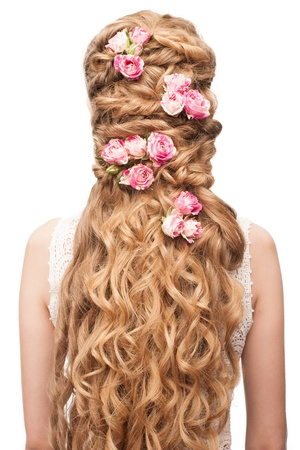 Blond Hair. Beautiful Caucasian Woman with Curly Long Hair. Bridal hairstyle decorated by flowers photo