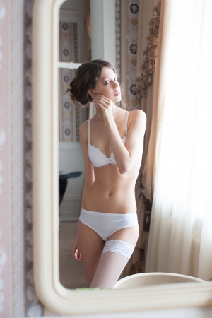 Beautiful slim woman in white lingerie looking on herself in mirror in her bedroom  photo