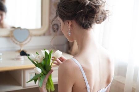 Portrait of young beautiful bride with bouquet of white tulips preparing to her wedding day photo