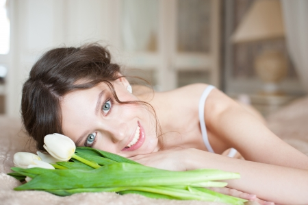 Closeup shot of happy beautiful bride with bouquet of white tulips lying on the bed in her bedroom photo
