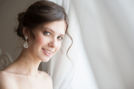 Closeup portrait of young beautiful bride in her wedding day photo