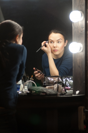 Mirror reflection of a young caucasian woman applying makeup photo