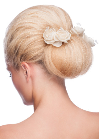 Portrait of young beautiful woman with elegant hairstyle, over white background. Rear view photo