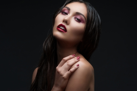 Fashion studio shot of beautiful woman with stylish makeup and manicure photo