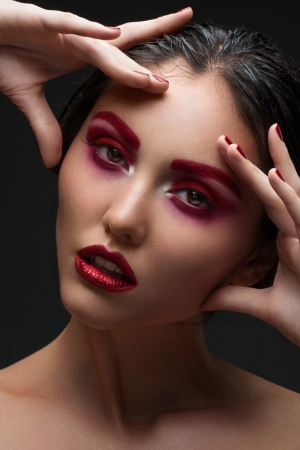 Fashion studio shot of beautiful woman with stylish red makeup and manicure touching her face photo