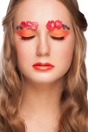Close-up portrait of young beautiful woman with orange lipstick and small red flowers on her eyebrows, over white background photo