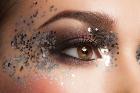 glitter makeup: Maquillaje de ojos. Primer plano de la hermosa mujer de ojos con maquillaje del brillo. Maquillaje de fantas�a, pesta�as falsas