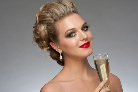 Beautiful smiling woman with fashion bright makeup and hairstyle with a glass of champagne. Party, drinks, christmas concept photo