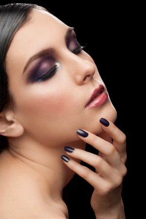 Fashion studio shot of young beautiful woman with bright violet makeup and manicure photo