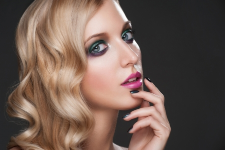 Close-up studio portrait of young beautiful woman with bright fashion makeup and manicure photo