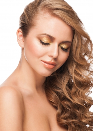 Close-up studio portrait of young beautiful woman with stylish golden makeup and hairstyle photo
