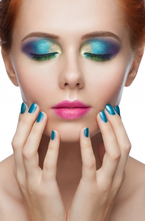 Closeup portrait of woman with colorful peacock style makeup and turquoise manicure touching her face. Bright eye makeup, closed eyes photo