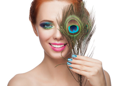 Woman with colorful makeup and peacock feather, isolated on white background photo