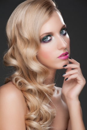Portrait of young beautiful woman with bright fashion makeup, manicure and curly hairstyle photo