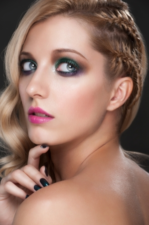 Portrait of young beautiful woman with bright fashion makeup, manicure and creative hairstyle with tress photo