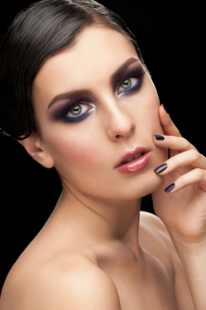 Fashion studio shot of young beautiful woman with bright makeup and manicure photo
