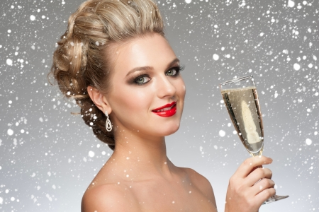 Beautiful smiling woman with fashion bright makeup and hairstyle with a glass of champagne. Party, drinks, christmas concept Stock Photo - 24641222