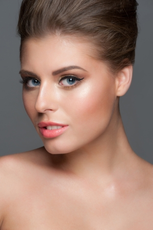 Fashion stuio shot of young beautiful woman with stylish golden makeup photo