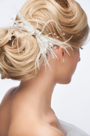 Portrait of attractive young woman with beautiful bridal hairstyle and stylish hair accessory, rear view photo