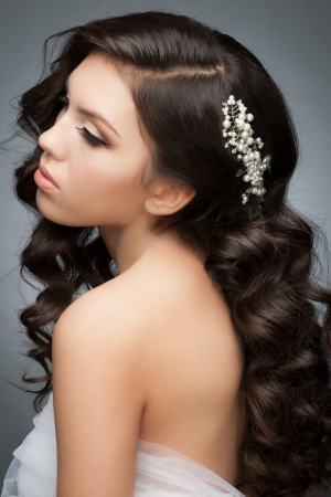 Portrait of a pretty young woman with a beautiful bridal hairstyle and makeup. Brunette with long wavy hair photo