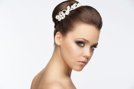 Portrait of a pretty young woman with a beautiful bridal hairstyle and makeup photo