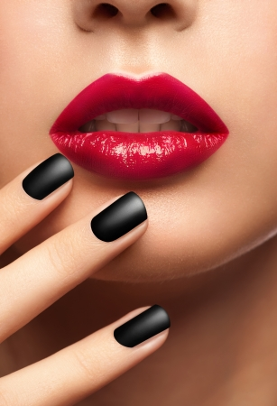 Close-up shot of sexy woman lips with red lipstick and beautiful black manicure photo