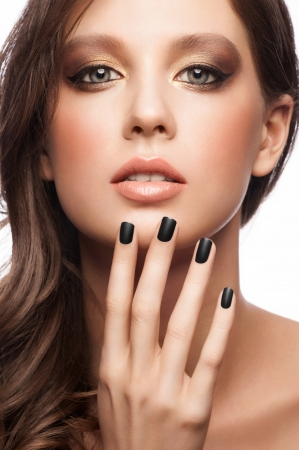 Fashion studio portrait of young beautiful woman with bright makeup and black manicure, isolated on white photo