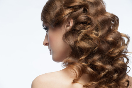 Portrait of attractive young woman with beautiful hairstyle. Girl with long curly hair, rear view photo