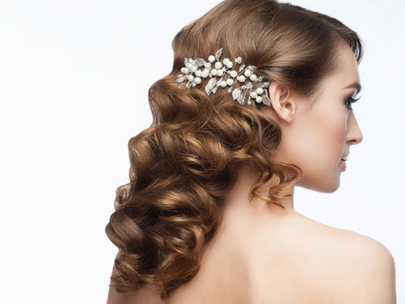 Portrait of attractive young woman with beautiful hairstyle with stylish hair accessory. Girl with long curly hair, rear view photo