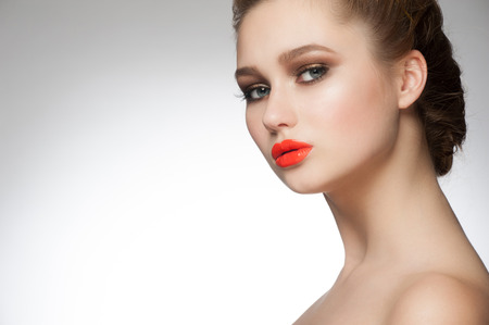 Portrait of young beautiful woman with stylish makeup with orange lipstick photo