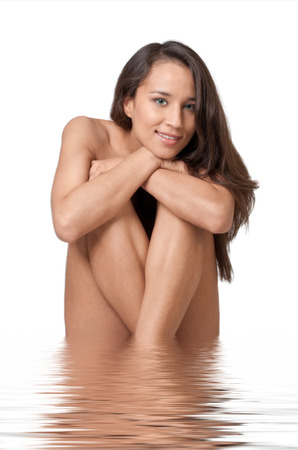 Naked beautyful woman with long brown hair sitting in water, isolated on white. Beauty treatment concept  photo