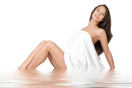 Young beautiful woman wearing white towel sitting in water. Beauty treatment concept  photo