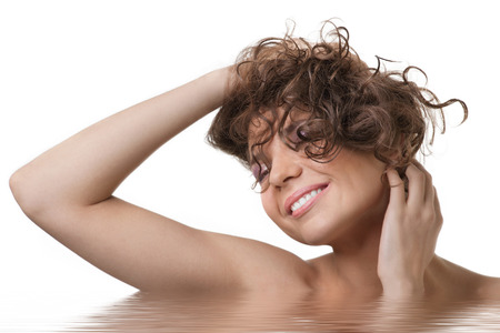 Portrait of  beautiful young woman in water with curly hairs touching her face. Beauty treatment concept photo