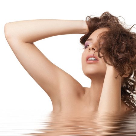 Portrait of the beautiful young woman with curly hairs in water. Beauty treatment concept  photo