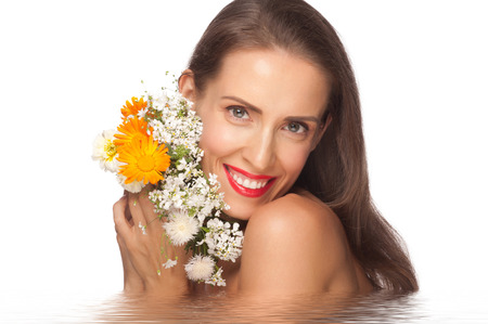 sexy mature women: Portrait of beautiful middle aged woman with smooth healthy skin holding flowers in water Stock Photo