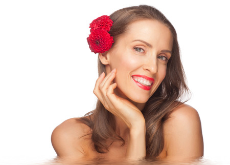 beautiful middle aged woman: Portrait of beautiful middle aged woman with smooth healthy skin holding flowers in water. Beauty treatment concept